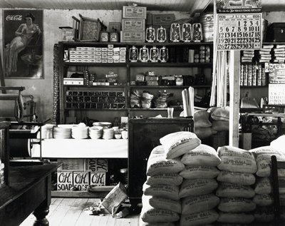 large sacks of flour at right; counter stacked with cups and plates at left; shelves with various objects including boxes of canning jars, lanterns and dust pans against wall; two calendars at right; Coca-Cola sign with woman in gown in ULC