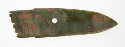 Ceremonial blade; flenged tang (handle). Mottled green jade; the blade is slightly raised in the middle and the central ridge continues to the tip of the blade; the edge (tang) ends in slightly projected flenge of 'tooth' pattern. Traces of clay-like substance.