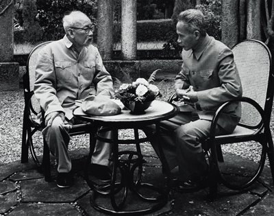 two men seated outdoors at a table with a bowl of flowers, man at L has long white beard and wears glasses; man at R has hands folded