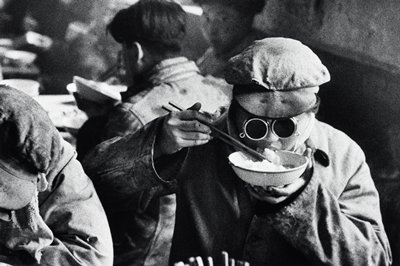 person wearing cap and goggles, eating rice from a bowl with chopsticks; other figures at L
