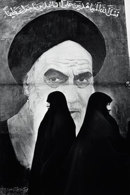 mural portrait of the Ayatollah Khomeini; two women wearing long black head scarves stand in front of mural, facing opposite directions