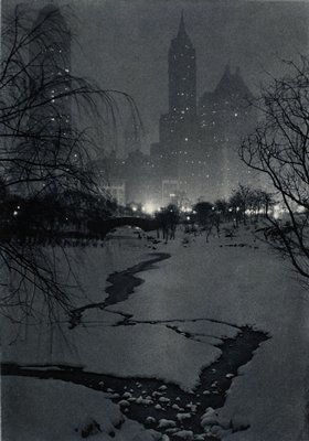 winter night scene with snow, trees and bridge in foreground; bright lights at base of buildings in background.