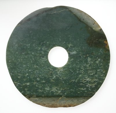 Mottled green jade with brown marks, damaged along edge. Used in imperial services for the worship of Heaven, used as emblems of rank and tokens of friendship.