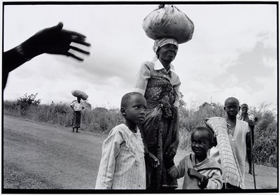 woman on road with three children and carrying a bundle on her head