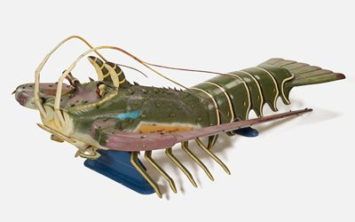 Coffin representing a rock lobster with five pairs of jointed limbs, two long antennae, which are hinged, and two paired feelers on top. It is painted a green color with six white and black stripes around the body, orange and white paint at sides, and light-purple painted anntenae. The upper body is covered in spines and has a rough texture.