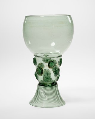Green tinted glass; flared foot with hollow stem; round prune decorations with rounded bowl