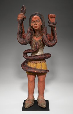 standing female figure wearing short pleated yellow skirt, belt with tan disks, silver blouse, red and black bolero jacket, silver shoes, and silver necklace with flower or star pendant; woman has long black hair and wide eyes; body intertwined with one snake, another snake around woman's neck; attached black metal mount