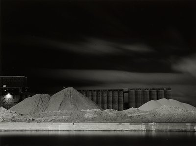grain elevators behind large piles of sand (?--may be dirt or snow); water in foreground; tall building at left; dark sky with clouds