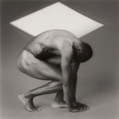 black and white photograph of a nude man crouched in front of a grey ground and a white diamond shape