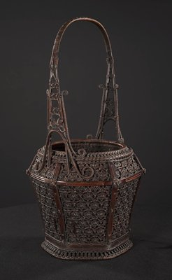 hexagonal basket with tapered, round mouth; squarish handle; patterned weaving along top of handle; swirling, elegant supports and decorations along handle; ornate, star-shaped close weaving pattern; carving on supports; large copper lined bamboo cylinder with grate at top