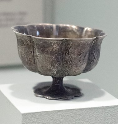 cup of stem, lotus shape, lotus motif stamped with background stipple covering outside; interior plain; silver.