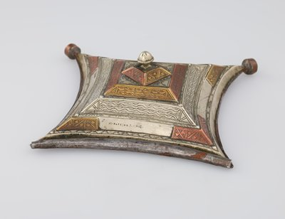 four sided pendant with curved sides; slightly domed; stepped; open tube at top for hanging cord; round elements on bottom points; some delicate engraved patterns of zigzags, wavy lines, triangles, football shapes; copper and brass elements; round finial at center; engraved inscription at top right of center