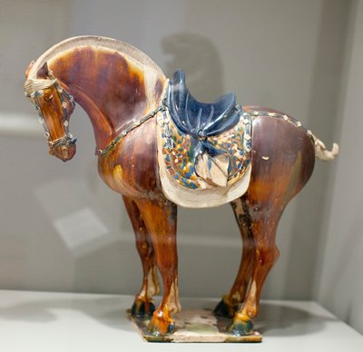 Horse with clipped mane and tail. ca 725 A.D. Glazed pottery tomb figure, one of a pair, on a flat base. The trappings, including double saddle pads and a saddle draped with a knotted cloth, are decorated with Sassanian motifs. Brown glaze with patches of manganese in oxidized areas.