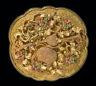 Jeweled gold presentation b ox; surface chased with swastika fret design. Cover of box bears crutch and gourd, emblems of Taoist philosopher Li T'ieh-Kuai, surrounded by delicately spun gold blossoms picked out with small cabochon rubies, sapphires, and green jade. The emblems dime in filigree. One of a set of eight presented to the Emperor Ch'ien Lung in the 43rd year of his reign.