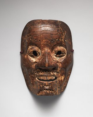 mask of male face with large nose, round eyes with carved out eyeholes; narrow grin with top teeth visible; wrinkles in forehead; holes drilled into eyebrows, moustache, and chin possibly once for hair