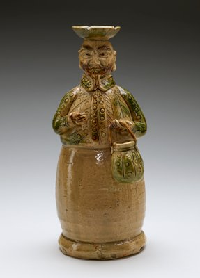 ceramic candle holder; male figure holding basket in PL hand, and remnant of an object in PR hand; exaggerated, pointed facial features; large brown eyebrows, moustache, and pointed goatee; wearing green top coat with incised patterns; figure becomes round from waist to base; lower half is beige; leaf design on head for candle
