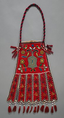 felt bag with beaded designs and wide, beaded fringe; one side is red with floral beaded motif; vine motif on the fringe; other side is navy blue with two beaded birds; black and red twisted cord; tassels with shell beads