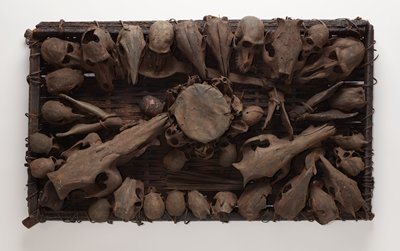 rectangular panel on woven base; small drum at center surrounded by vertically-placed small animal skulls; four small possibly primate skulls around top edge of drum; large long-handled spoon below drum; plant fibers bundled into a whisk at top; two largest skulls from animals with long snouts at top corners; 28 skulls of various types and sizes around edge of panel, all facing inward; two jawbones at left center, one jawbone at right center; covered overall with burnt black patina; NOTE: proper configuration of piece is horizontally with the spoon at the top and the whisk at the bottom--description and condition report written with the piece upside down, with the spoon at the bottom