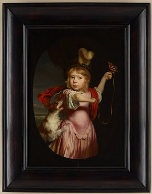 little boy with shoulder-length blonde hair and brown eyes, wearing a green cap with a tall white feather and a pink skirted garment with a white blouse underneath and a red cloth over his shoulders, holding a brown finch on his extended PL index finger; finch has a ribbon attached to its leg, which the boy holds in his PR hand; jumping brown and white spaniel with its mouth open at boy's PR hip; image in an oval with brown border