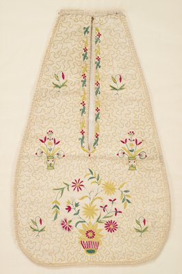 pouch; roughly teardrop-shaped with squared-off top with long vertical slit opening from top; gold, green, red and white embroidery; white fabric embroidered overall with gold organic lines; scrolling plant forms and flowers around edge of opening; four pair of drooping red and white buds; one pair of symmetrical flowers in green and gold vases; large asymmetrical flower bouquet at bottom center in a red and white striped container; received mounted, framed in gilt frame and glazed