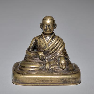bronze lama seated on rectangular base; PR hand holding edge of robe; PL hand resting palm up on knee; underside of base consists of copper insert; black patina
