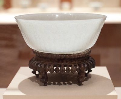 Bowl of white Camphor jade, carved in a XVIII century Tibetan form suggesting a Chrysanthemum, a design that came to Tibet from India, and was later introduced into China by Tibetan Carvers and brought to Peking by Ch'ien Lung. The nephrite jade has a beautifully lustrous quality. Former Classification: Jade