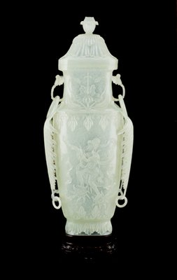 Vase, carved camphor jade, with cover.  Ovate form carved at shoulders with two delicte twigs encircled by loose ring handles, and flanked by fur pendant fern leaves extending to the upper foot.  On the two body panels carved fighures of Bodhisattvas, one blowing a horn and standing upon two prayer wheels; the other holding a pole lantern.  About the foot a double collar of foliage.  Floral fluting and finial on cover. This piece worked to extreme translucency. Probably a copy of a bronze form.