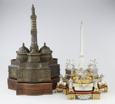 The inkstand is a replica of the Quirinal Monument in Rome and was made to commemorate its erection during the pontificate of Pius VI. The composition includes an Egyptian obalisk, and four horse tamers that can be swung from their bases on levers to reveal an inkwell and a sandbox; Sphinxes' headdresses conceal candle sockets; one of the drawers contains an assortment of tromp l'oeil engravings; two doves can be made to kiss by means of a lever located in the fountain; the inkstand has a leather carrying case that resembles a medieval fortified town, with gates, battlements and a bell tower.