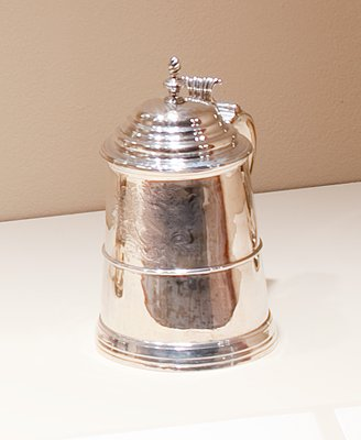 tankard with tapering cylindrical body, domed lid with cast spiral finial, scrolled thimb piece, plain handle with cast tip in form of mask; a band of plain molding surrounds the body just below mid-point, and the molded base is reeded at top; an unidentified coat-of-arms is engraved on the front, opposite the handle