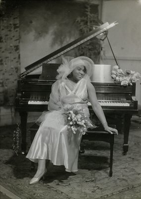 woman with large hat holding flowers, seated at a piano