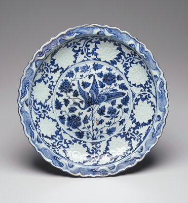 Blue-and-White dish, porcelain; decorated in a deep blue in the center with a large peahen flying amongst peonies, the cavetto molded with a band of peonies in white in a blue ground, the rim with a border of stylized waves and a molded foliated edge; the reverse has a typical wide unglazed base with a short foot ring and the exterior is decorated with a band of scrolling lotus