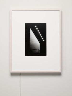 image of round lights above a blank white billboard with a railing beneath; light colored frame with lightbox; bottom portion of lightbox cord detaches