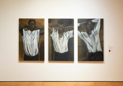 unframed triptych; all three images are of an individual man with his arms raised up near his head and his elbows out, wearing a white shirt and black pants with a brown background; man's position varies slightly between images a: both his hands on the back of this neck; collared shirt; eyes looking to viewer's right b: one hand on the back of his head and the other is curled above his shoulder; his eyes are downcast c: one hand on the back of his head and the other on the side of his head above his ear; he looks out to the viewer
