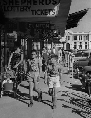 "Black and white photograph of two boys wearing ties and shorts walking down a ""mainstreet"" type sidewalk"