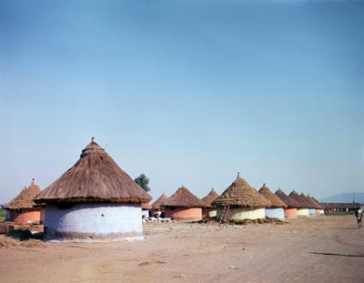 Color photograph of round buildings in blue, red and light green, with pointed, thatched roofs; clear blue sky