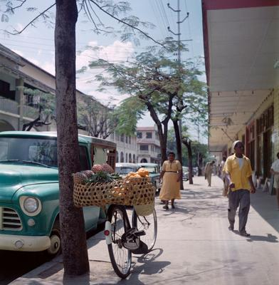 Color image of a bike with a basket filled with fruits leaned against a tree in a street scene; figures walk along the side walk