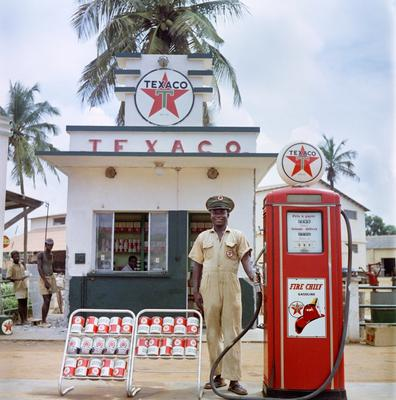 Color image of a man in a uniform standing outside of a Texaco gas station