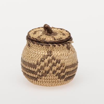 Miniature olla basket with flared rim and cover; coiled. Design consists of three horizontal bands broken by three checkered chevrons. Cover has a swastika design. Colors are natural and black.
