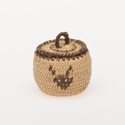 Miniature round basket with cover; coiled. Design consists of three animal heads, probably buffalo. Colors are natural and black.