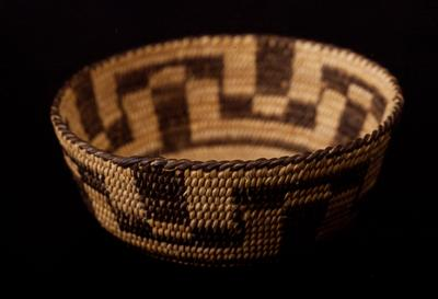 miniature basket, shallow with sloping sides; finely coiled; design consists of alternating reversed T-bars in a continuous pattern around the sides, in natural and black (possibly a variation of a squash-blossom design.)