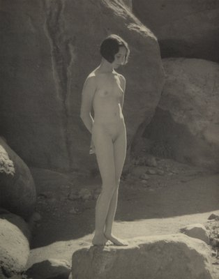 nude young woman with wavy bobbed hair standing, slightly turned to PL, with arms behind her back, looking down; standing on the edge of a large rock with boulders behind
