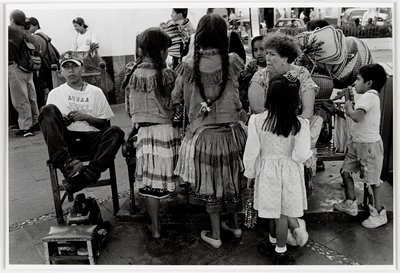 boy at left in tennis t-shirt and Raiders hat sitting in a chair with shoe shine materials in front of him; group of women and children clustered around a bench at right
