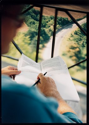 notebook with hands of man in foreground; view looking down at window at top; large margin on L