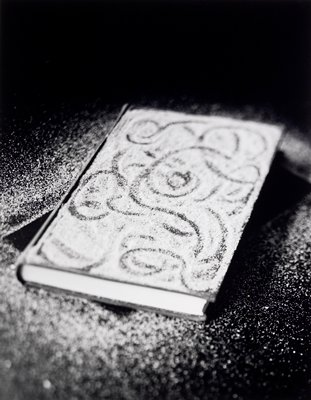 hard-cover book with sand on cover; swirling designs traced in sand