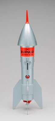 silver space ship (a) with red rubbery tip on nose; coin slot in nose cone bottom; spring mechanism to fire coin into slot; red rocket engines in base; one contains key (b)