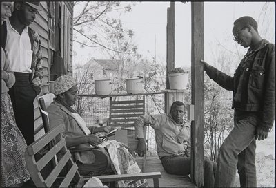 two young men at right, one standing and one seated on edge of porch; woman with a scarf on her head, cutting cardboard, seated in a chair on porch; standing young man and woman and left edge