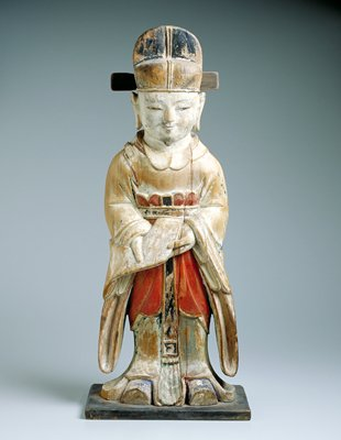 polychrome wood statue of a Confucian scholar standing, holding a book (?) downward at waist toward the viewer, wearing a long flowing blue robe, red waisted skirt with black belt and a black hat