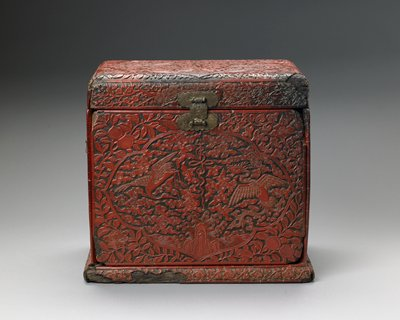 hinged covered red lacquer box with a removable front panel; tray under cover, six drawers behind panel; flying crane and phoenix over rock and crashing waves, main design at top and sides of box