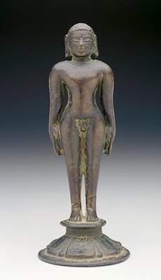 nude male figure with short hair and elongated earlobes standing rigidly upright on a base with incised designs