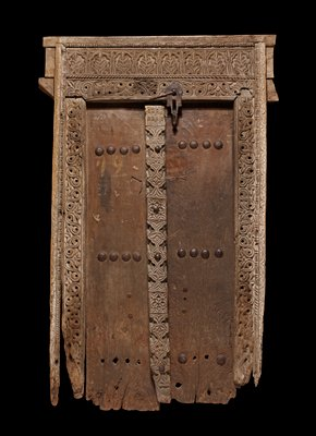 large door; carved jambs, lintel and central post on door; two complete rows remaining of large iron fasteners on door surface; only two remain in lower row; iron chain, plate and securing pin at top right center of door; four pins along center post on door